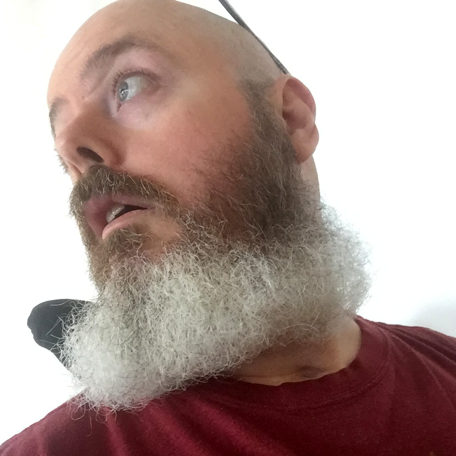 This is a selfie, taken from a low angle and looking over my right shoulder, wearing a red t-shirt and a mid-length, largely greying beard.